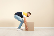 Full Length Portrait Of Young Man Lifting Carton Box Near Color Wall. Posture Concept