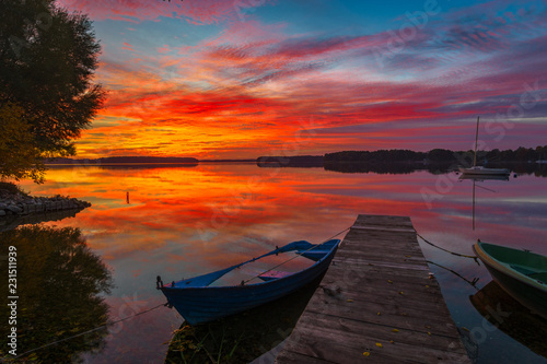 Türaufkleber Hochrote boats by the wooden bridge over the lake during a beautiful sunset