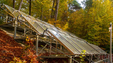 Solar Panels Surrounded By An Autumn Forest