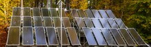 Solar Panels Surrounded By An Autumn Forest-Panorama