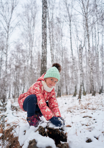 girl in a bright hat in the winter forest