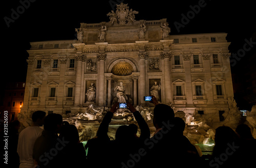 Foto op Aluminium Rome Sightseeing in Rome. Tourists visit and take pictures of the wonderful Trevi Foutain with night illumination