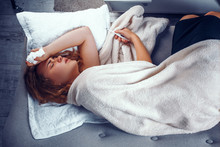 Exhausted Woman Is Laying In Bed And Holding A Thermometer To Check Temperature. Sick Blonde Girl Laying In Bed Under Wool Blanket With A Hand With A Napkin On Her Head.