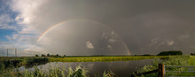 Panorama Of A Bright Rainbow Over The Dutch Countryside