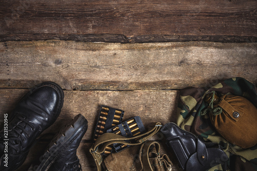 Fotografiet Army military uniform, weapon, holster, pistol, flask, boots on wooden background