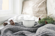 Cozy Winter Morning Breakfast In Bed Still Life Scene. Steaming Cup Of Hot Coffee, Tea Standing Near Window. Christmas Concept. Pillows, Pine Cones And Fir Tree Branch On Wool Plaid.