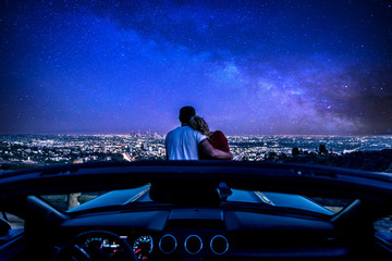 Fototapeta Couple watching sunset from popular view point in Los Angeles, California. Sitting on the sport convertible car hood