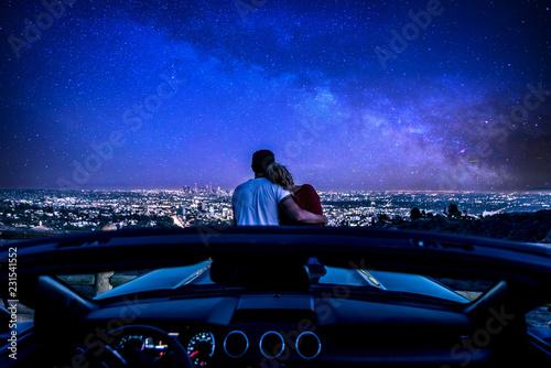 Naklejka premium Para oglądając zachód słońca z popularnego punktu widzenia w Los Angeles w Kalifornii. Siedząc na masce sportowego kabrioletu