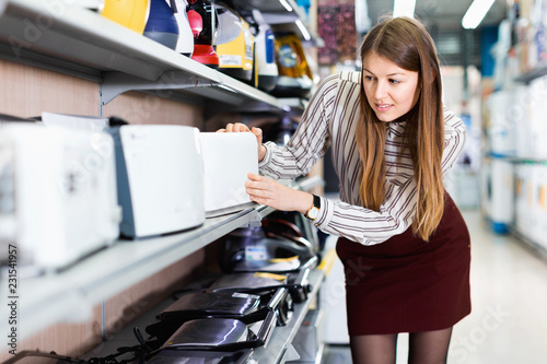 Fotografía  Modern female housewife choosing new toaster in domestic appliances section