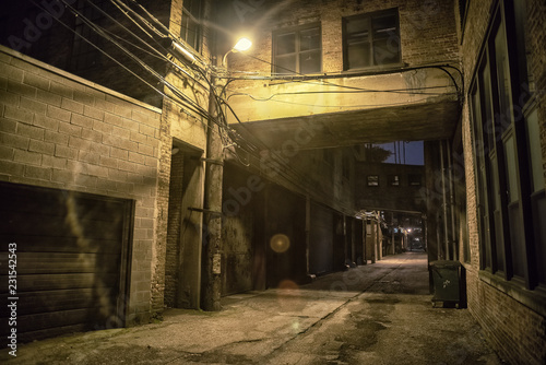 Dark and scary downtown urban city street alley scene with an eerie vintage industrial warehouse factory skyway at night