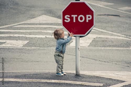 Foto niño parado en señal de stop en la carretera