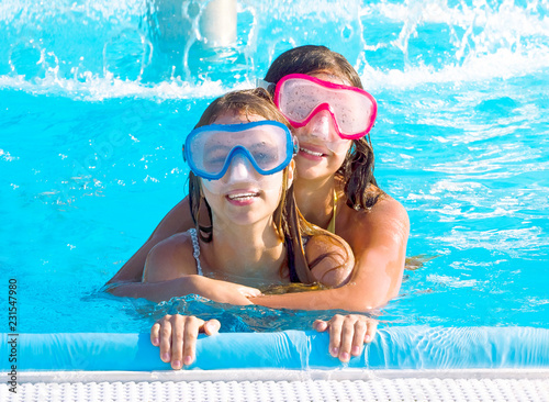 Fotografia  Happy young children, sisters, relaxing on the side of a swimming pool wearing blue and pink goggles