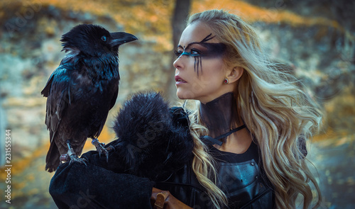 Fototapeta Beautiful black crow, Viking blonde woman with shield and sword, braids in her hair