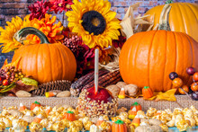 Popcorn Peanuts Candy Corn And Red Candy Apple On Blue Table With Background Of Yellow Sunflowers Orange Pumpkins Nuts Berries And Fall Flowers On Burlap