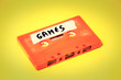 canvas print picture - A vintage cassette tape (obsolete music technology), orange on a yellow surface, angled shot, carrying a label with the handwritten text Games.