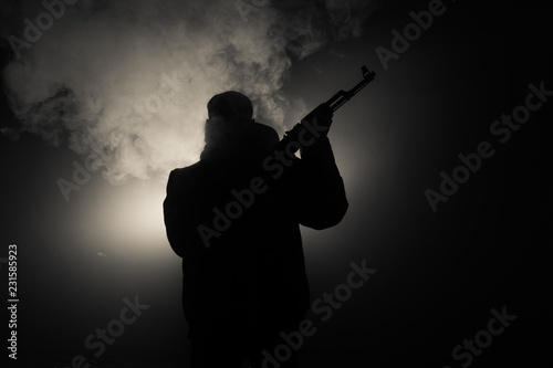 Fotografie, Tablou  Silhouette of man with assault rifle ready to attack on dark toned foggy background or dangerous bandit in black wearing balaclava and holding gun in hand
