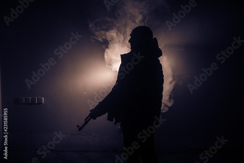 Photo Silhouette of man with assault rifle ready to attack on dark toned foggy background or dangerous bandit in black wearing balaclava and holding gun in hand
