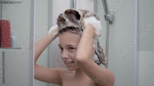 Vídeo de Smiling young girl bathing under a shower at home. Beautiful teen girl taking shower and washing in the bathroom. Happy child washing head, face and body with water. no Adobe Stock | Adobe Stock