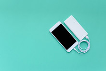 Smartphone Charging With White Power Bank Through USB Cable On Turquoise Background Top View With Copy Space
