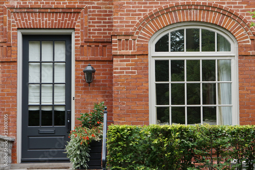 front door and window of old house with weathered bricks