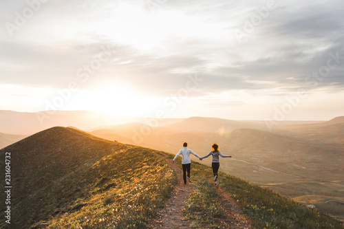 Photo  Young couple running together by sunset hill with amazing mountain view