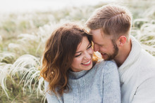 Happy Young Loving Couple Sitting In Feather Grass Meadow, Laughing And Hugging, Casual Style Sweater And Jeans