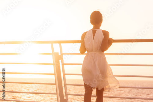 Cruise ship vacation woman luxury travel watching sunset over ocean . Elegant lady in white dress on deck enjoying view of famous holiday destination. Girl on getaway happy relaxing.