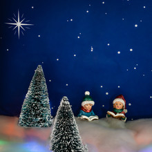 Two Carolers Practice In The Forest Under A Starry Night.