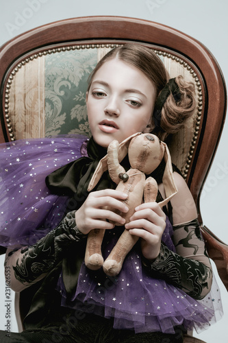 Beautiful girl child model in fashionable clothes holding a rabbit toy Tablou Canvas