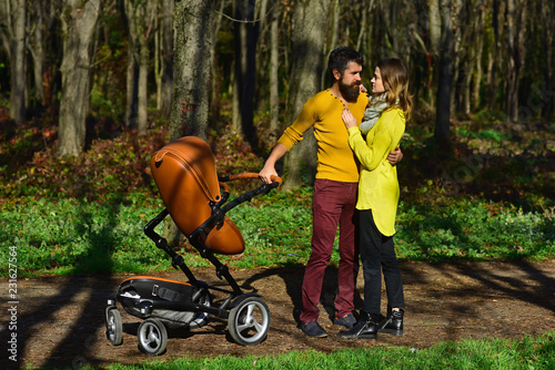 Fényképezés  Married couple enjoy walking in spring park with baby pram