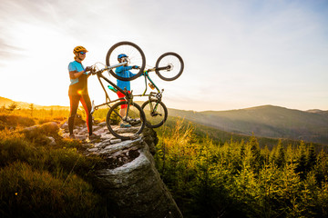 Fototapeta Sport Mountain biking women and man riding on bikes at sunset mountains forest landscape. Couple cycling MTB enduro flow trail track. Outdoor sport activity.