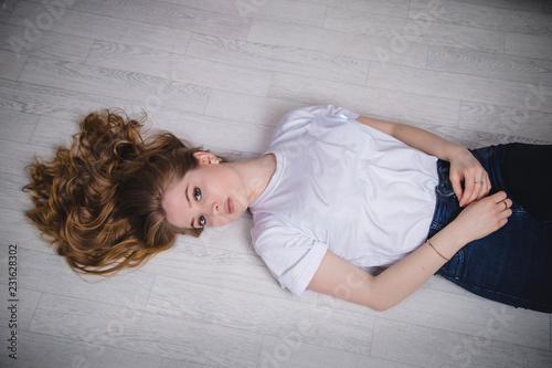 Fotografie, Tablou  Girl in a white t-shirt lying on the floor