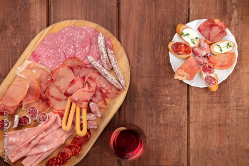 Poster Assortiment Charcuterie Tasting. An overhead photo of many different sausages and hams, cold cuts, shot from the top on a dark rustic background with a glass of red wine and copy space