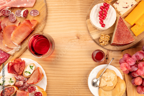 Poster Assortiment Charcuterie Tasting. A photo of many different sausages and hams, lunch meats, and a cheese platter, shot from above on a rustic background with a glass of red wine and copy space