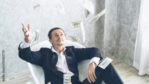 Fototapeta Happy business man very rich guy throw money dollar bills in air like rain money bill and banknotes US dollar bill on the bathtub - business success concept obraz