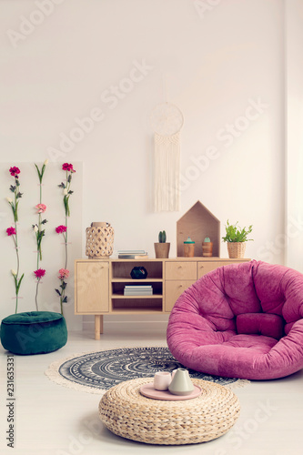 Patterned carpet in stylish boho interior with pink comfortable armchair and wooden furniture, real photo with macrame on the white wall