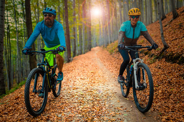 Fototapeta Cycling woman and man at Beskidy mountains autumn forest landscape. Couple riding MTB enduro track. Outdoor sport activity.