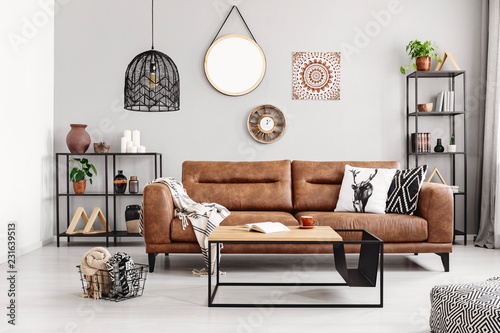 Obraz Leather sofa with pillows and blanket in the middle of elegant living room interior with metal shelves and modern coffee table, real photo - fototapety do salonu