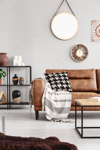 Fotografia  Vertical view of warm ethno living room with leather couch with patterned pillow