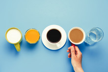Woman's Hand Takes A Cup With Coffee With Milk Group Of Healthy Drinks, Orange Juice, Coffee, Water, Yogurt On A Blue Background. Flat Lay Still Life Table Top View