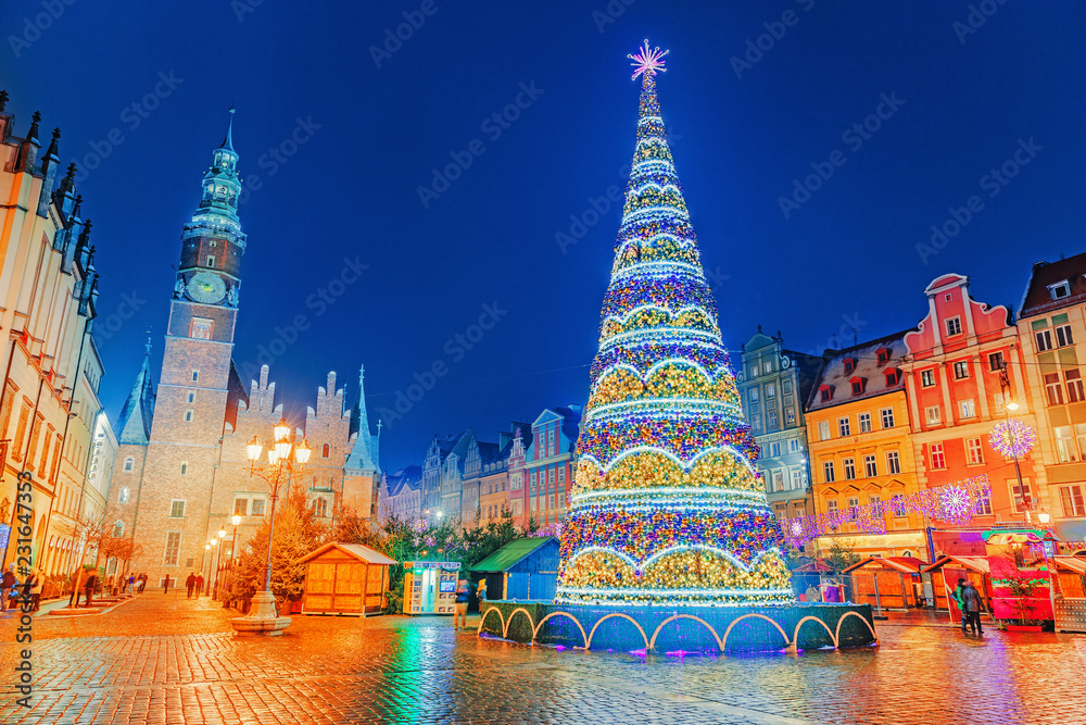 Fototapety, obrazy: Illuminated Christmas tree at central Square of old city on Christmas Market in Wroclaw, Poland. New Year ambiance, illuminated and ornamented festive city. Night scene. European traditions.