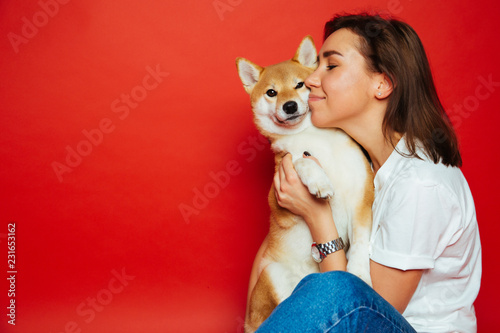 Fototapeta Cute brunette woman in white t shirt and jeans holding and embracing Shiba Inu dog on plane red background