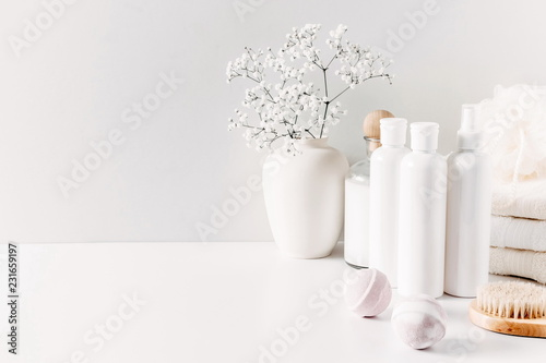 Obraz na płótnie Soft light bathroom decor for advertising, design, cover, set of cosmetic bottles, bath accessories, white small flowers in vase, towel on white wooden shelf