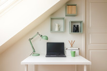Modern Workspace Interior. Laptop Computer, Retro Lamp And Office Accessories On A White Desk. Cozy Attic / Loft Apartment With Skylight Window Letting The Sun Shine In.