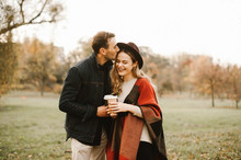 Young Couple In Love Hugging, Having Fun And Smiling In The Park On A Sunny Autumn Day And Drinking Tea