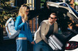 man putting baggage into car with smiling girlfriend near by