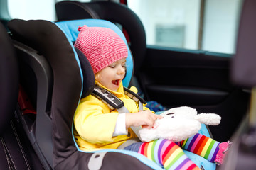 Fototapeta Adorable baby girl with blue eyes and in colorful clothes sitting in car seat. Toddler child in winter clothes going on family vacations and jorney. Safe travel, children safety, transportation