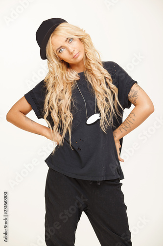 blond swag girl in fashionable black look stands on white