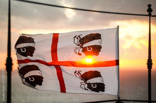 Bandiera dei quattro mori della Sardegna, su sfondo cielo al tramonto Wallpaper Mural