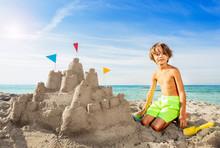 Happy Boy Building Big Sand Castle On The Beach